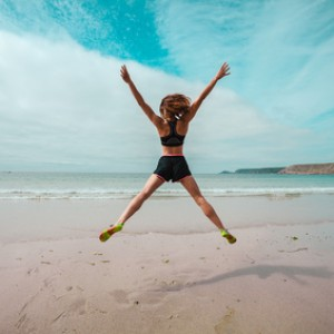 Young woman doing star jumps on the beach